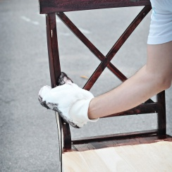 staining chair with painter's mitt