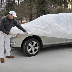 man putting on car cover